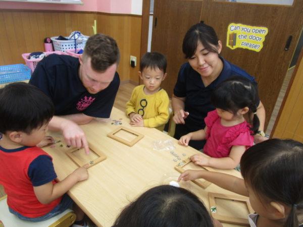 フォトフレームにパズルピースを貼っているお子さまと講師