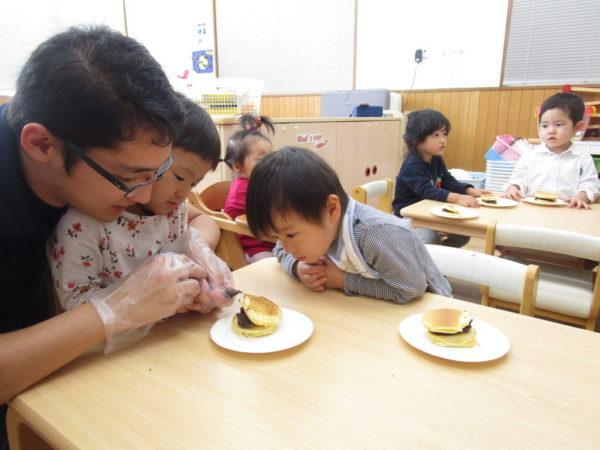 モンスターパンケーキに目をチョコペンで描いているお子様と講師