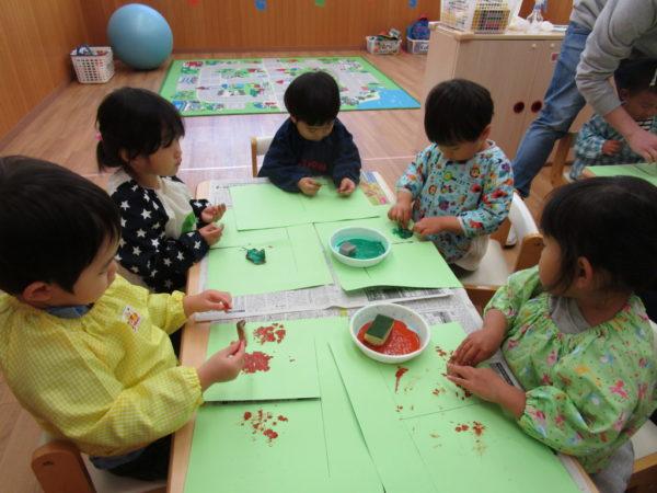 ペタペタと絵具のついた落ち葉を紙にスタンプするお子さま
