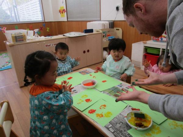 講師の絵具だらけの手を見て様々なリアクションを取っているお子さま